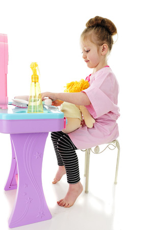 An adorable preschool in an oversized cosmetology smock, sitting at a toy hairdresser's station with a doll on her lap.  On a white background. Imagens - 80894623