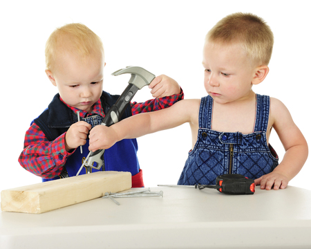 Two adorable toddler boys standing at a table with a short 2 x 4 board, nails, a tape measurer and a toy hammer.  One is looking somewhat annoyed while the other puts a nail where he things it belongs  On a white background. Imagens