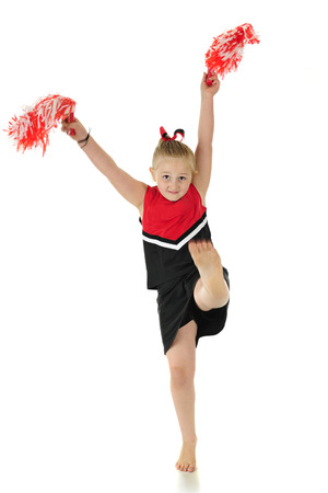 A young elementary cheerleader in uniform, kicking her bare foot.  Motion blur on foot and pom poms. On a white background. Imagens - 80845053