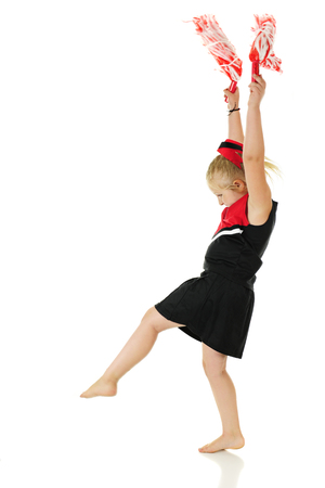 black cheerleader: Profile of a young elementary cheerleader holding her pom poms high as she steps in preparation for doing a cartwheel.  On a white background.  Motion blur on the pom poms.