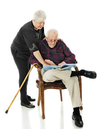 A senior man looking at an opened book, a senior woman looking over her shoulder and pointing to something. On a white background. Imagens