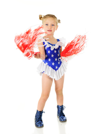 pom poms: An adorable preschooler in a stary outfit happily waving red and white pom poms.  Motion blur on the pom poms.  On a white background. Stock Photo