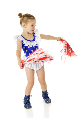An adorable preschooler in a blue outfit with white stars and ruffles, and sparkly blue shoes.  She's waving red and white pom poms.  Motion blur on the pom poms.  Isolated on white. Imagens - 115278946