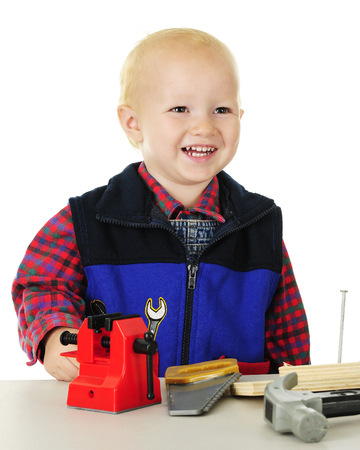 Closeup image of a happy tollder standing at his tool table with a toy vice, saw, and hammer.  On a white background. Banco de Imagens