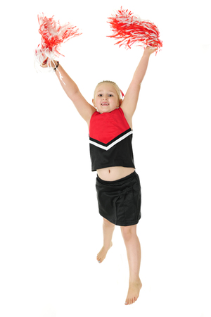 An elementary cheerleader, barefoot but in uniform, jumping high as she practices a cheer.  On a white background. Stock Photo