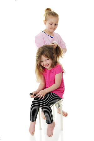 An elementary girl is brushing her laughing, preschool sisters hair. Focus on laughing girl.  On a white background.