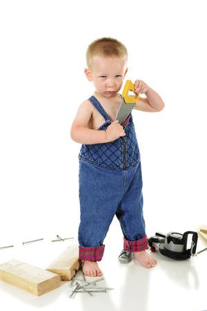 """Un bambino """"colpevole"""" che guarda pigro mentre cerca di nascondere il giocattolo visto che stava giocando con. Su uno sfondo bianco. Archivio Fotografico - 81172172"""