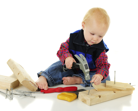 An adorable toddler carefully setting the nail hes getting ready to hammer.  On a white backgound. Banco de Imagens