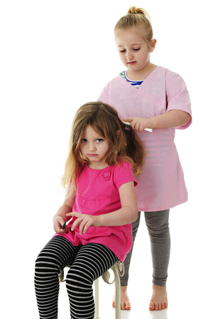 An unhappy preschooler pouting as her young elementary sister brushes her hair. On a white background. Imagens