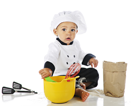 An adorable baby boy dressed as a chef and sitting among baking equipment and flour.  On a white background.