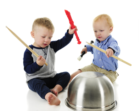 A two-toddler rhythm and music band. Both boys hold a recorder and drumstick in their raised hands, and upside down drum bowl in front of them.  On a white background. Banco de Imagens