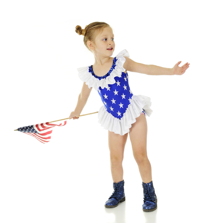 An adorable preschool girl dressed in ruffles and stars and holding an American flag, beckoning others.  On a white background.