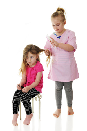 A preschooler making a face as her elementary sister brushes out her long hair. Focus on sitting girl.  On a white background.