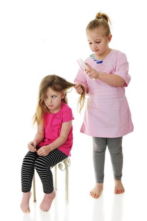 Ein Vorschüler macht ein Gesicht, als ihre elementare Schwester ihre langen Haare ausstürzt. Konzentriere dich auf sitzende Mädchen. Auf einem weißen hintergrund. Standard-Bild - 81638640