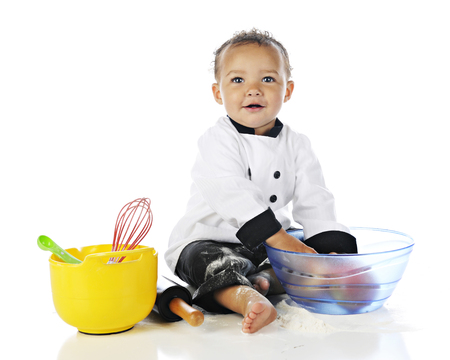 An adorable baby boy wearing a chefs jacket and balck pants, playing with apples and cooking utensils, and messed up with white flour.  On a white background.