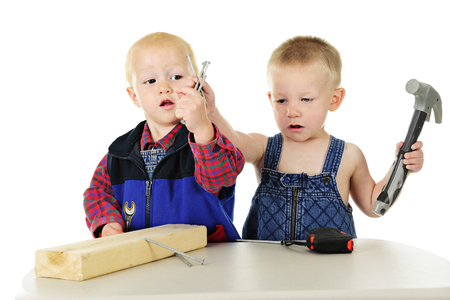pretending: Two toddler boys each grasping the same handful of large nails as they play hanyman with a block of wood and tools.  On a white background. Stock Photo