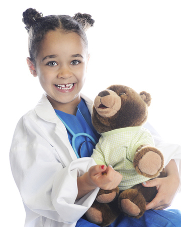 A happy elementary girl pretending to be a health care provider taking care of a patients teddy bear.  On a white background.