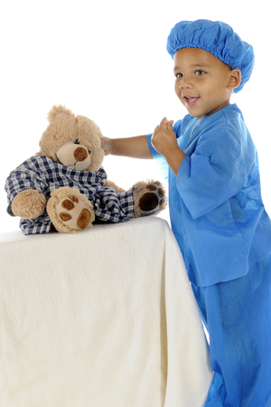 An adorable preschool doctor in blue scrubs, happily taking care of his toy bear whose wearing a hospital gown.  On a white background. Banco de Imagens