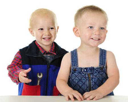 Two adorable toddlers standing together at their work table. One wears a plaid flannel shirt and tool vest, the other is in overalls with no shirt. Focus is on boy on the left. Imagens - 81196346