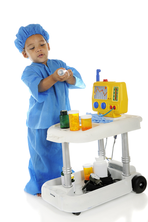 An adorable preschool doctor in blue scrubs adjusting a large srynge of fluids from his emergency cart.  On a white background. Banco de Imagens