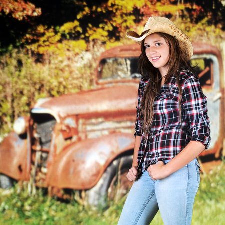 A pretty young teen in a cowboy hat standing by a rusty old truck by an autumn woods.