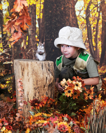 An adorable young elmentary girl sneaking up on a nut-carrying chipmunk in the autumn woods.