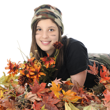A pretty young teen ion camouflage hat and pants, relaxed in autumn flowers and leaves.  On a white background.