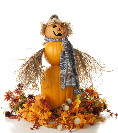 An orangescarecrow made up of 3 pumpkins, straw arms, a long brown scarf and topped with a straw hat. The scrarecrow is surrounded by colorful fall foliage. Isolated on white.