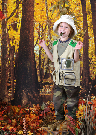 An adorable kindergarten girl happily blowing her whistle while exploring an autumn woods.