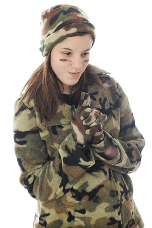 A young teen girl in camouflage happily contemplating the shoot as she stands with her fingers locked in a gun position.  Isolated on white. Imagens - 115279024