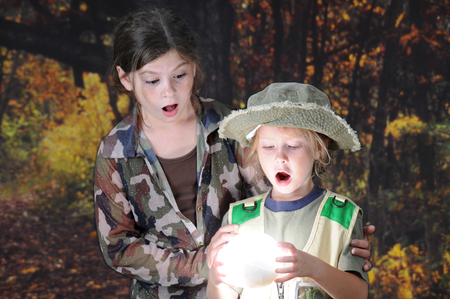 Young sister explorers holding and amazed by a brilliant light sphere found in a darkened woods.