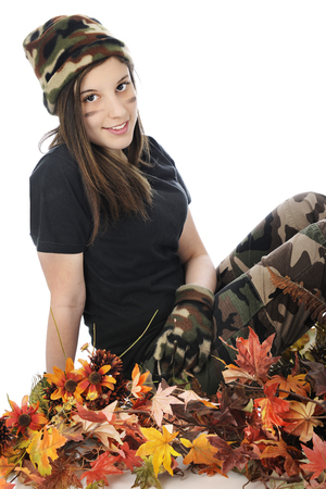 A beautiful young teen in camouflage happily sitting among colorful fall foliage.  On a white background. Imagens - 115279029