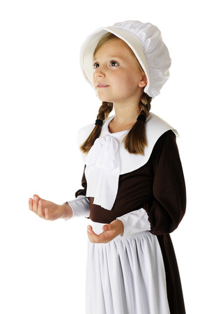 A beautiful elementary pilgrim looking heavenward as she gives thanks to the Lord.  On a white background. Banco de Imagens