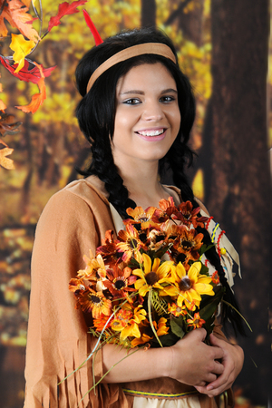 A beautiful teen Indian Maiden happily carrying a large bouquet of fall flowers.  Shes in a colorful forrest setting.