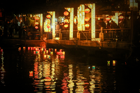A lighted bridge in Vietnam, with homemade lanterns floating on the river