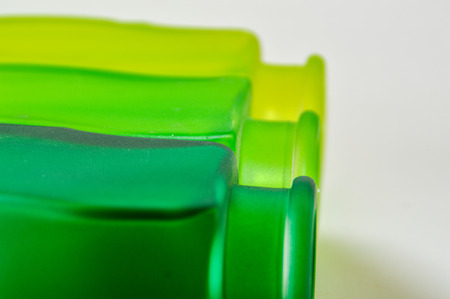 side by side from dark green to light green glass bottles on white background Stock Photo