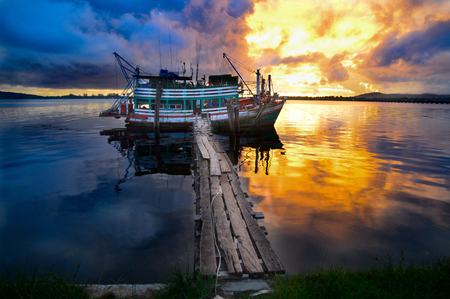 A Cambodian fishing boat is reflected in the water with your fantastic sunset Stok Fotoğraf