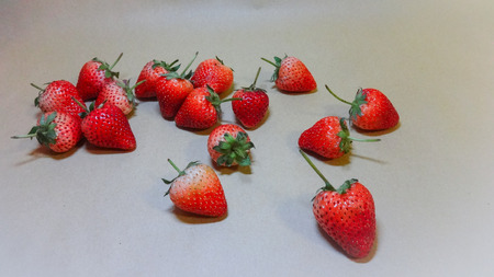 fresh ripe summer strawberries laid out on a white background
