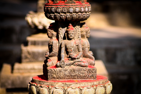 A Buddha statue with red powder coated in the Swaymabunath Temple in Kathmandu, Nepal
