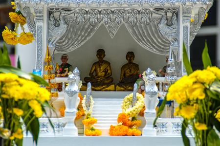 Three golden Buddha statues in a shrine decorated with flowers Stock Photo - 98481498