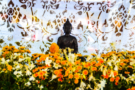 A black Buddha with flowers decorated against a white background Stock Photo
