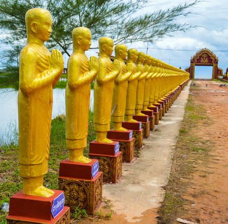 A temple complex with golden buddha statues at the entrance outside of Koh Kong, Cambodia