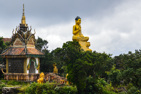 A golden statue overlooks the temple complex outside Kampot, Cambodia
