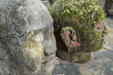 Two Buddha heads on the edge of a temple at Angkor Wat Stock Photo