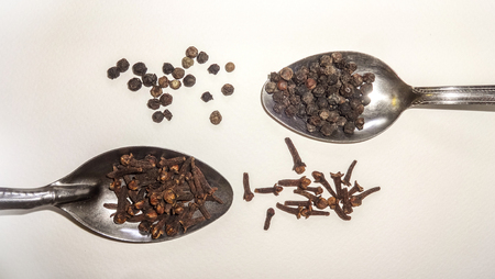 Clove and pepper arranged side by side on two spoons and white background