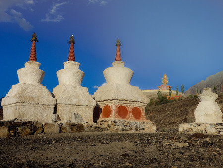 small stupas in the foreground with the giant Buddha statue from the Diskit Gompa in the background, Diskit, Diskit valley, Ladakh, India Stock Photo