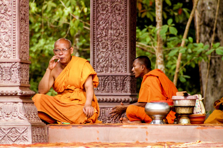 Two Buddhist monks sit in the shadow of a temple and rest Editorial