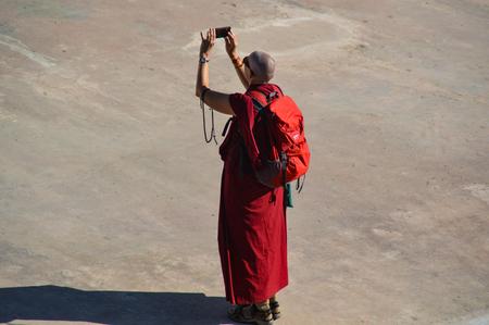A Buddhist monk in red robe take a selfie, Kathmandu, Nepal