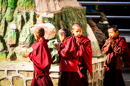 Four young Buddhist monks in red robes are encircling the sacred temples of the Swayambhunath temple complex with praying hands