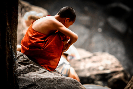 A young Buddhist monk sits aloof, dreaming to himself